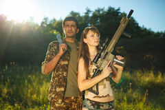 White girl and an Arab man in camouflage with a weapon in the ha Stock Image