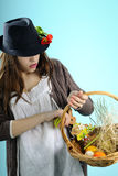 White girl arranging easter decorations. Teenager girl with black hat arranging easter decorations in basket Royalty Free Stock Photography