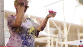 White girl dropping powder and dancing at holi colour festival stock footage