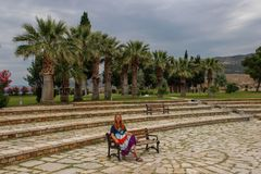 A white girl in a hippie dress sits and rests on a bench in Pamukkale National Park stock photos