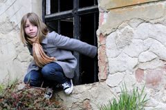 White girl playing on medieval wall. Single child playing in front of old window Royalty Free Stock Photos