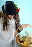 White girl searching easter decorations. Teenager girl with black hat searching easter decorations in basket Stock Photography