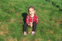 White girl sitting on green grass Royalty Free Stock Photos