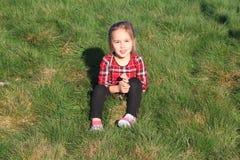 White girl sitting on green grass Stock Images