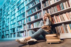 White girl near bookshelf in library. Student is holding books on her lap. royalty free stock photography