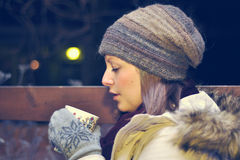 White girl in winter clothes blows on a tea cup. White smiling girl wearing the wool cap and mittens blows on the tea cup sitting on a bench in the evening Royalty Free Stock Photography