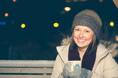 White girl in winter clothes drinks tea. White smiling girl wearing the wool cap and mittens drinks tea on a bench in the evening Stock Image