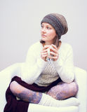 White girl in wool clothes drinks tea on the white chair. White smiling girl wearing the wool cap and mittens blows on the tea cup sitting on a bench in the Stock Photos