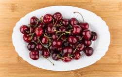 White glass dish with cherries on table Stock Photo