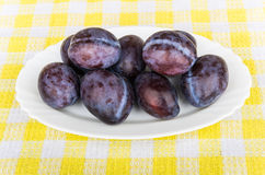 White glass dish with ripe plums on tablecloth Royalty Free Stock Photos