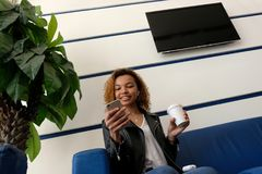 A happy beautiful African American girl with a white wireless earpiece in her ear is looking into the phone while sitting in the w. A white glass in the hand of stock images