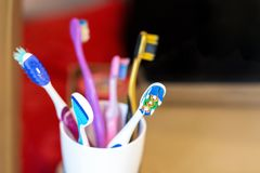 White glass with lots multicolored toothbrushes. Dental care and oral hygiene. Tongue cleaning. Big family concept.  royalty free stock photos