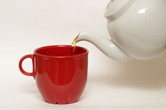 White glazed faience tea pot and red cup Stock Photos