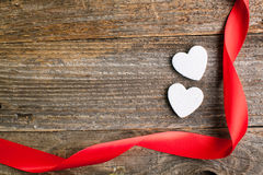 White glitter hearts with red satin ribbon on reclaimed wood, va Stock Images