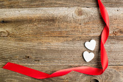 White glitter hearts with red satin ribbon on reclaimed wood, va Stock Image