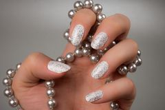 White glittered nails. Female hand with white glittered nails and pearly jewel is on gray background Royalty Free Stock Images