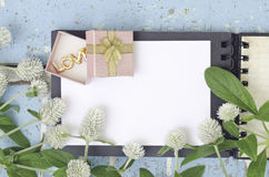 White Globe Amaranth flowers and gift box on open book Royalty Free Stock Photography