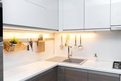 White gloss kitchen interior with worktop lighting. And hanging utensils stock photo