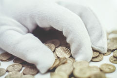 White glove with coins Stock Image