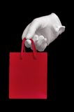 White glove holding red shopping bag Royalty Free Stock Photography
