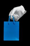 White glove with small blue shopping bag Stock Photo