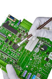 White gloved hands cleaning computer circuit board with brush is Royalty Free Stock Images
