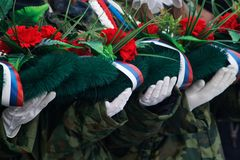 White-gloved hands hold a wreath and flowers in memory of those killed in wars and armed conflicts stock image