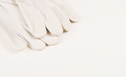 White Gloves. A pair of white gloves laying on white surface Stock Photos