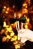 White Gloves champagne glass bow tie new year ball gold background. Studio royalty free stock image