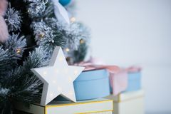 White glowing LED star near decorated Christmas tree and gift box. New Year festive atmosphere stock photos