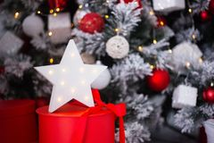 White glowing LED star on red gift box near decorated Christmas tree. New Year festive atmosphere royalty free stock photography