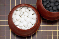 White go double convex yunzi stones in wooden bowl Royalty Free Stock Images