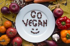 White go vegan plate with various vegetables top view. White plate with various vegetables and go vegan text top view Stock Photography