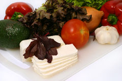 White goat feta cheese with baby salad on him. White goat feta cheese and raw vegetables Royalty Free Stock Photo