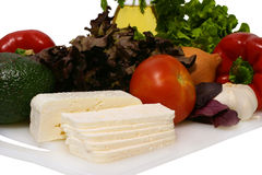 White goat feta cheese and vegetables on plate Royalty Free Stock Photography