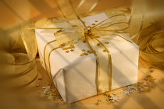 White and gold. Christmas gift wrapped with white and gold paper and bow royalty free stock image