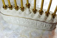 White and gold ceramic menorah base with gold metallic candles. Horizontal aspect, space for text Stock Photo