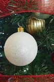 White and gold Christmas ball decorations. Hanging on a Christmas tree with some red ribbon royalty free stock photo