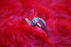 White gold diamond ring on red feathers. Romantic background. Closeup view stock photography