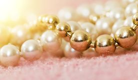 White and gold pearl necklace. Female gift on pink background Royalty Free Stock Image