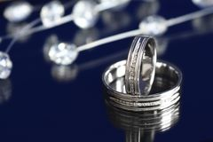 White gold rings. Pair of white gold wedding rings with diamonds on dark background Stock Images