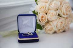 White gold, wedding bands, wedding rings from white gold in the blue box. Wedding jewelry, wedding preparation, a bouquet of white roses, white light Stock Image