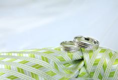 White gold wedding rings. Close up of pair of white gold wedding rings on top of green groom tie Royalty Free Stock Images