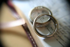 White gold wedding rings on bible. Two white gold bands on an open page in the bible, with soft macro effects and vignette Stock Photography