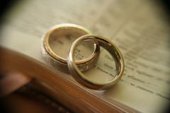 White gold wedding rings on bible. Two white gold bands on an open page in the bible, with soft macro effects and vignette Stock Images
