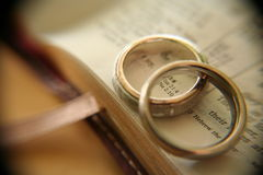 White gold wedding rings on bible. Two white gold bands on an open page in the bible, with soft macro effects and vignette Stock Photos