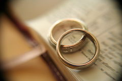 White gold wedding rings on bible. Two white gold bands on an open page in the bible, with soft macro effects and vignette Stock Image