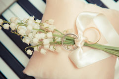 White gold wedding rings. With a bouquet of lily of the Valley Stock Photos