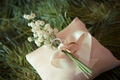 White gold wedding rings with a bouquet. Of lily of the Valley Royalty Free Stock Images
