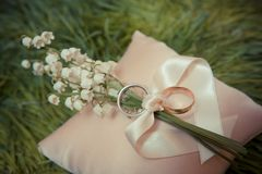 White gold wedding rings with a bouquet. Of lily of the Valley Royalty Free Stock Photos